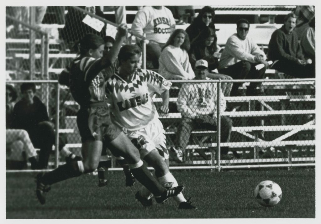 Photograph of two players fighting for the ball during a KU women's soccer game, 1995