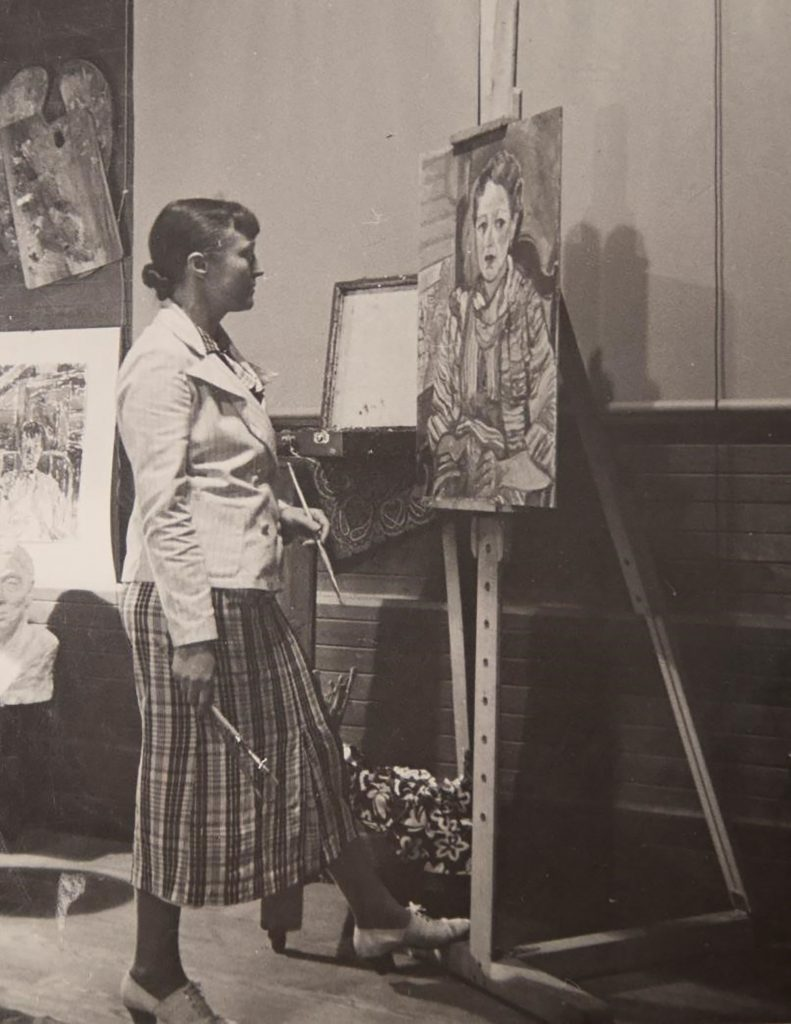 Artist Mary Huntoon stands before an easel, at work on a painting.