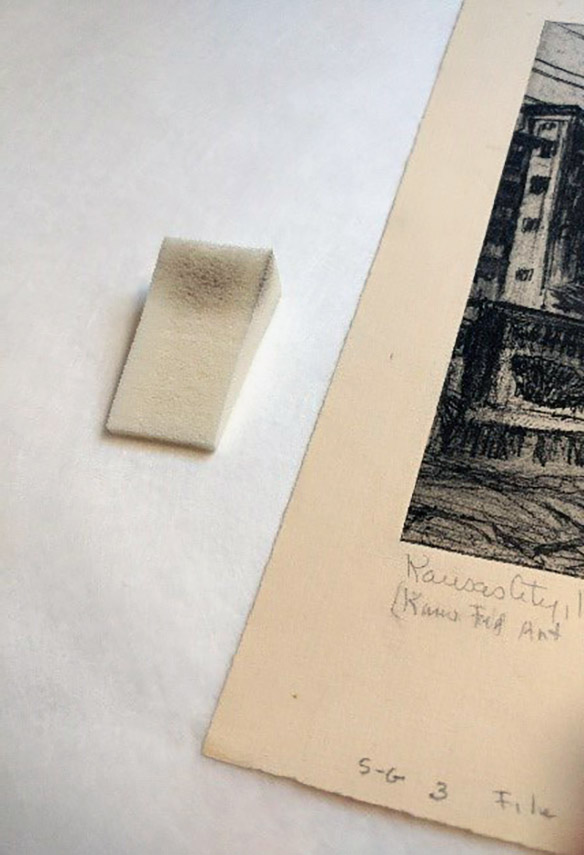 "A soft sponge is used to remove embedded surface dirt and grime from the Mary Huntoon print, ""Kansas City, Kansas Grain Elevators."""