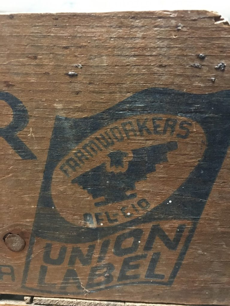 Photograph of the detail of a United Farm Workers' stamp on the wooden pickers' crate