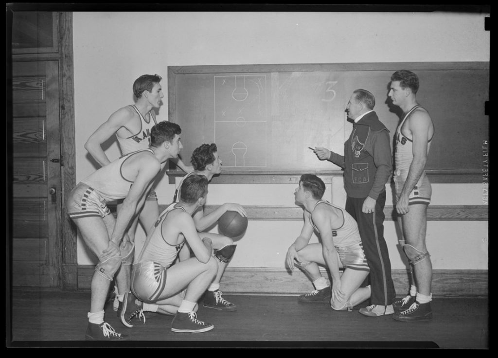 Photograph of Phog Allen drawing up a play on the blackboard while members of the basketball team look on, 1930s