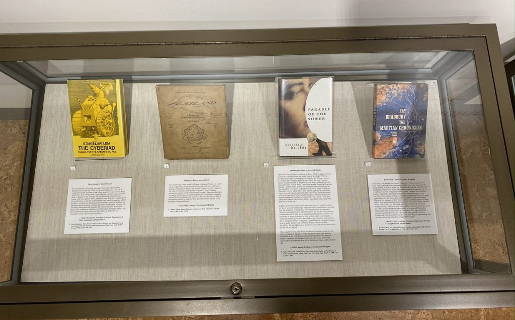 One of two cases containing faculty discussions of books that have been significant to them. From left to right: Vitaly Chernetsky (Slavic Languages and Literatures) on Stanisław Lem's The Cyberiad, Anna Neill (English) on Edwin Abbott Abbott's Flatland, Giselle Anatol (English) on Octavia E. Butler's Parable of the Sower, and Paul Scott (French, Francophone, and Italian Studies) on Ray Bradbury's The Martian Chronicles.