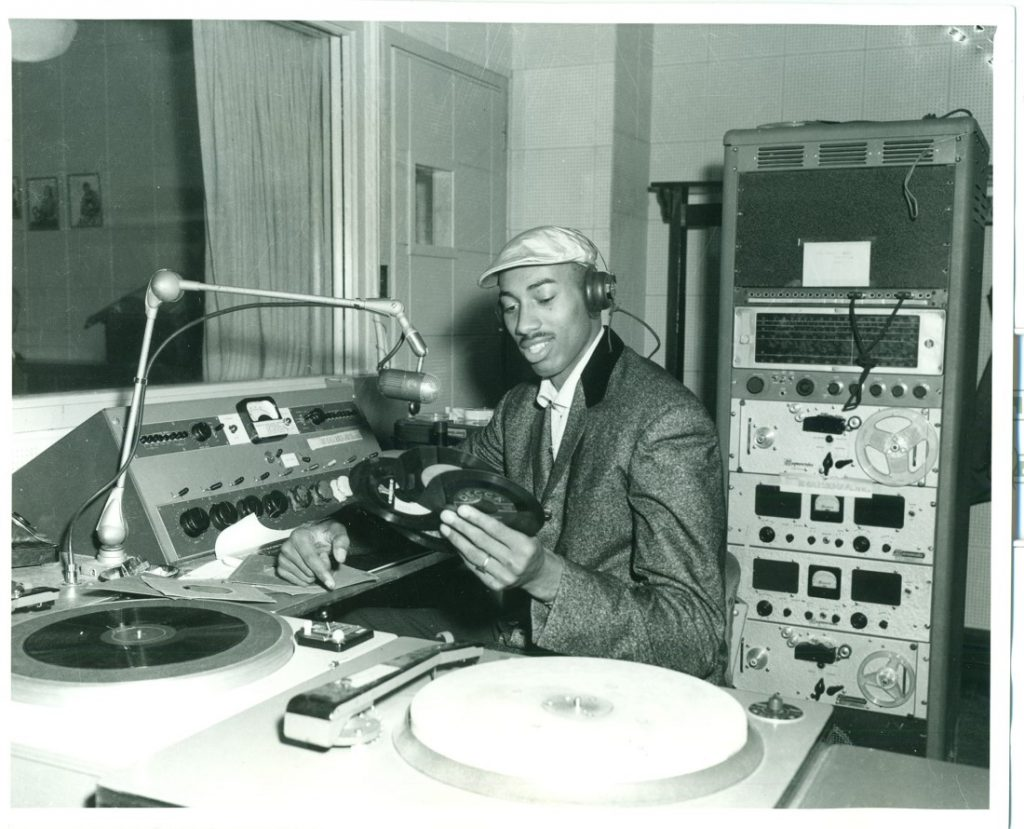 Photograph of Wilt Chamberlain looking at vinyl records in a radio studio, 1955-1958