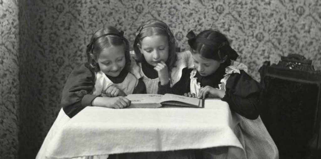 Photograph of three girls looking at a book, circa 1900