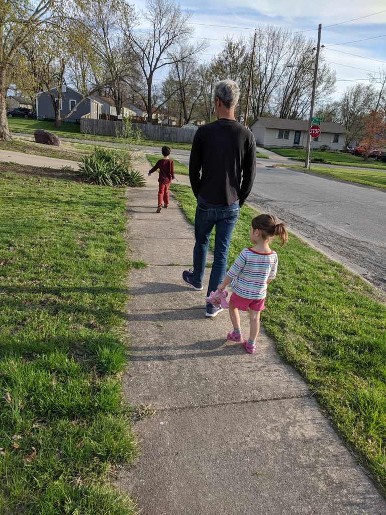 A father and two children on a walk in a residential neighborhood.