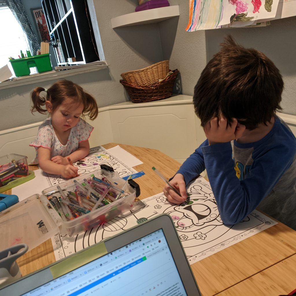 Two children color with pens and crayons at a kitchen table.