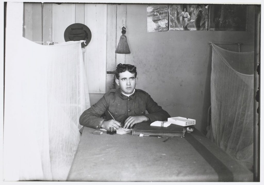 Photograph of a soldier writing a letter in a barracks room at Fort Riley, 1908