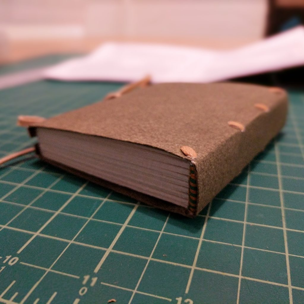 A small book lies on a cutting mat; the book is bound in the limp binding style, with a laced paper case, green and yellow endbands, and a fore-edge tie closure.