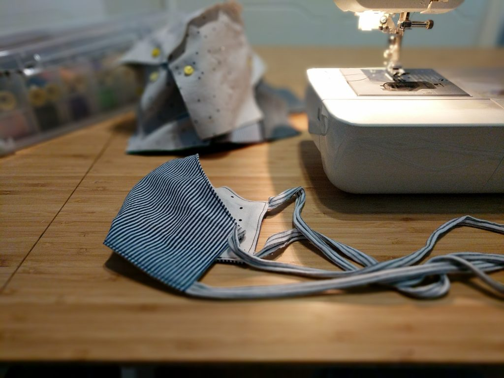 A handmade cloth face mask sits on a tabletop next to a sewing machine and other sewing supplies.