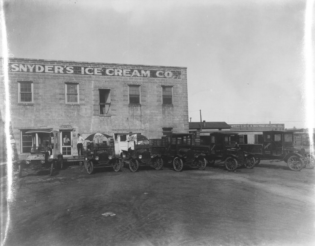 Photograph of Snyder's Ice Cream Co. (Wichita, Kansas) building exterior with ice cream trucks, circa 1920