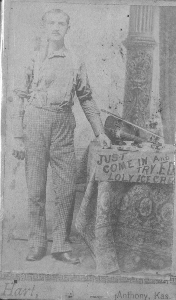 Photograph of a man with a violin and ice cream sign in Anthony, Kansas, circa 1880-1900