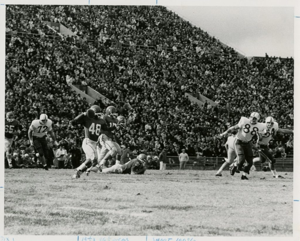 Photograph of Gale Sayers (No. 48) preparing to throw the ball during a KU football game, 1965