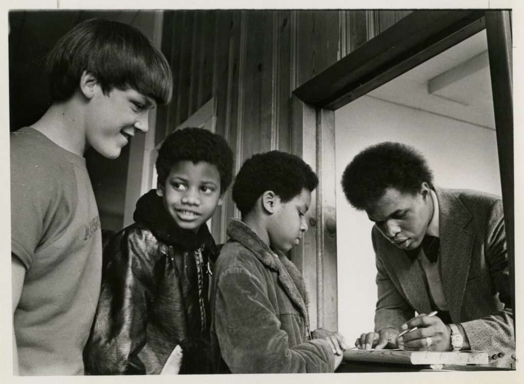 Photograph of Gale Sayers signing autographs for three fans, November 1974