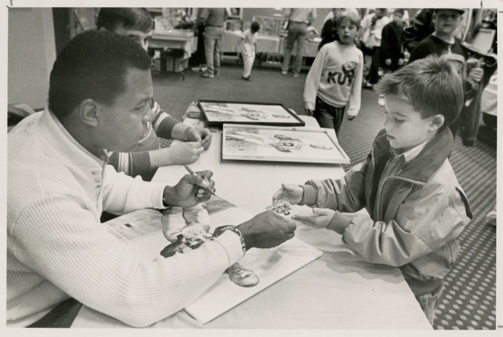 Photograph of Gale Sayers signing a fan's football card, October 1990