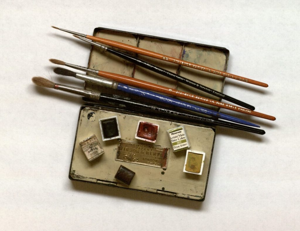 Photograph of a watercolor box with brushes and dry cakes of paint