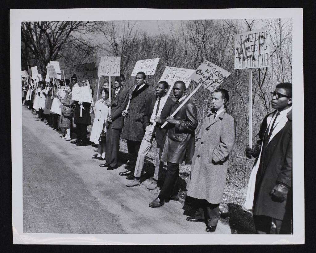 Photograph of a fair housing protest in front of the KU Sigma Nu house, March 21, 1964