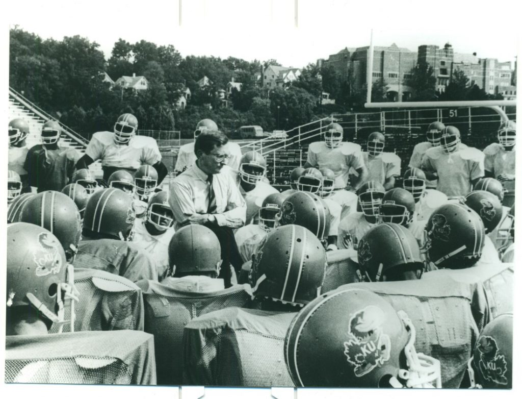 Photograph of Chancellor Gene Budig with the KU football team, 1980s