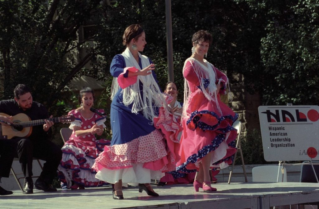 Photograph of two dancers at a music and dance performance sponsored by HALO in front of the Kansas Memorial Union, October 1997