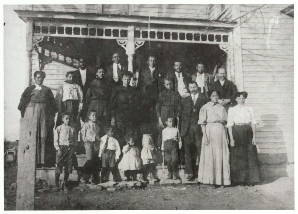 Photograph of the John Wilson family in front of a house, 1907