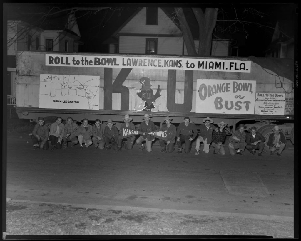 KU football fans kneeling in front of a decorated truck, 1947-1948