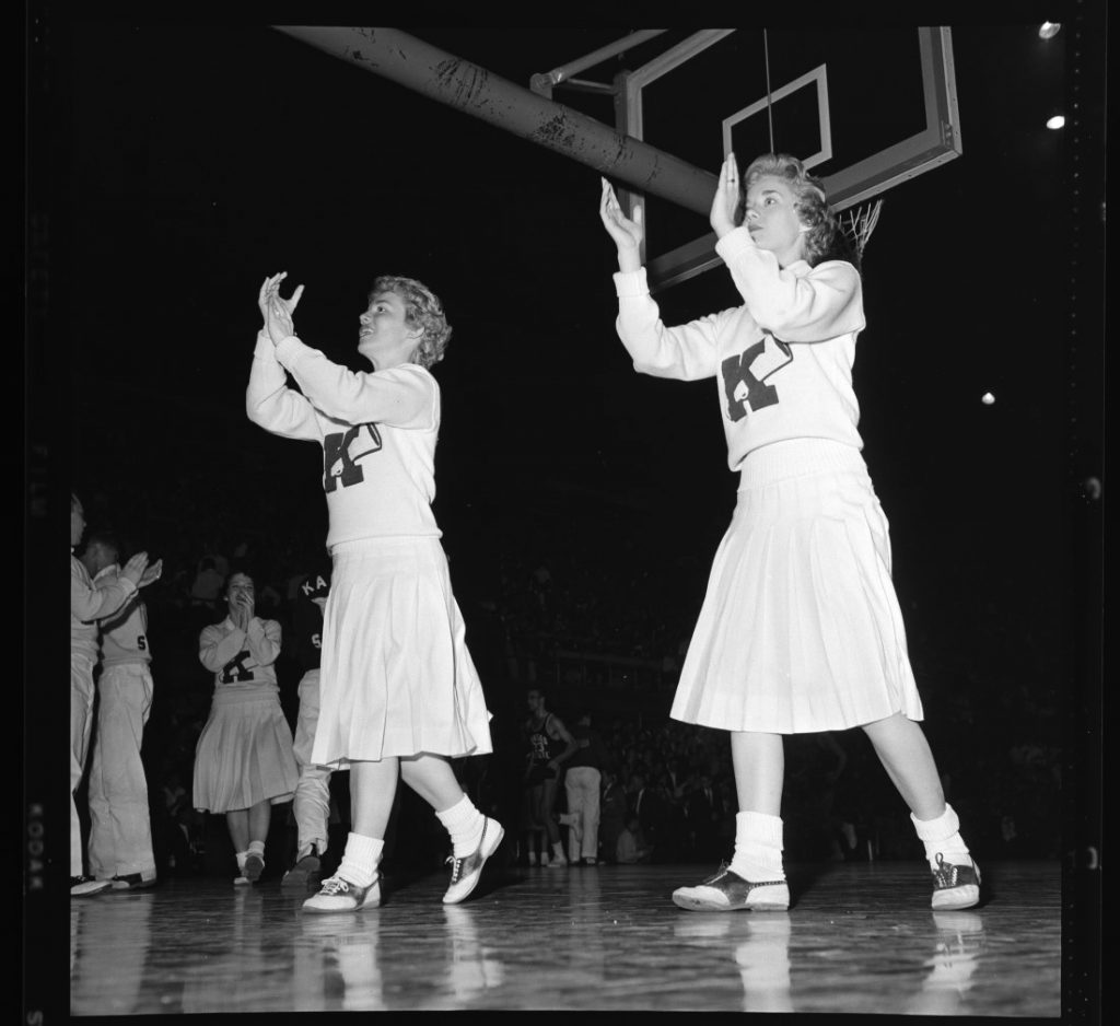 Photograph of KU cheerleaders clapping and cheering at a men's basketball game against Kansas State University, 1958-1959