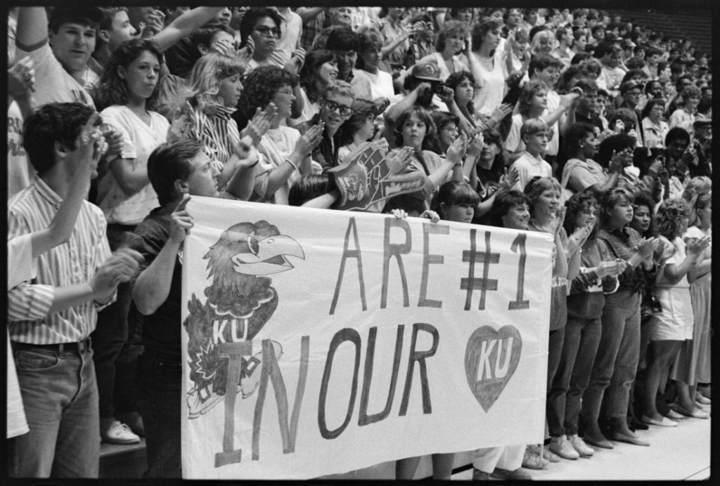"Photograph of KU basketball fans in the stands holding a sign with an image of a Jayhawk and the words ""Are #1 in our"" and an image of a heart, 1985-1986"