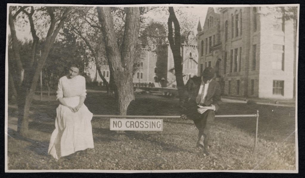 "Photograph of two KU students sitting on a ""No Crossing"" bar, 1900-1909"