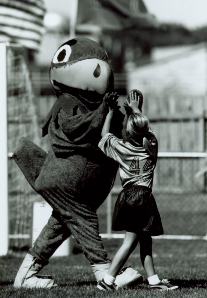 Photograph of Baby Jay high-fiving a young soccer play, 1996