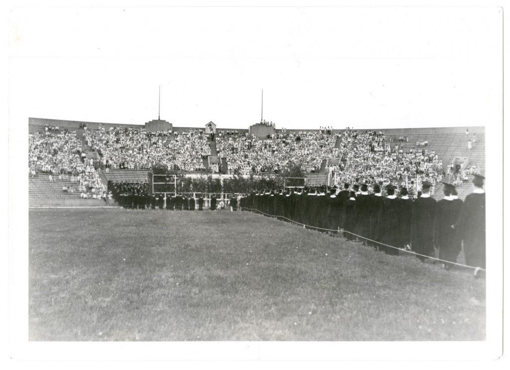 Photograph of KU graduates walking in Memorial Stadium for Commencement, 1933