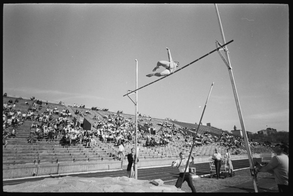 Photograph of an athlete at mid-height of a pole vault, 1965
