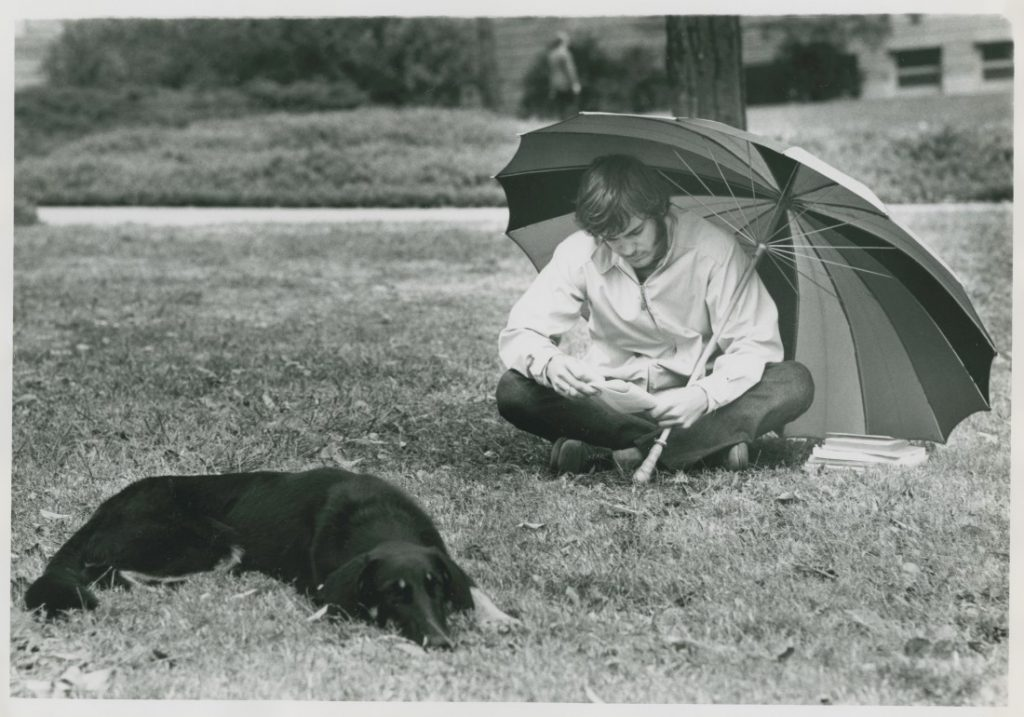 A black-and-white photograph of a male student sitting under an umbrella with a black dog.