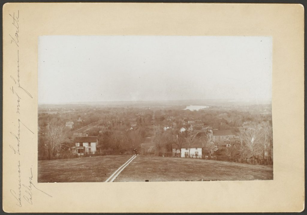 Black-and-white photograph of two people walking up Mount Oread on a pathway. Behind them, down the hill, are houses, trees, and unpaved streets.