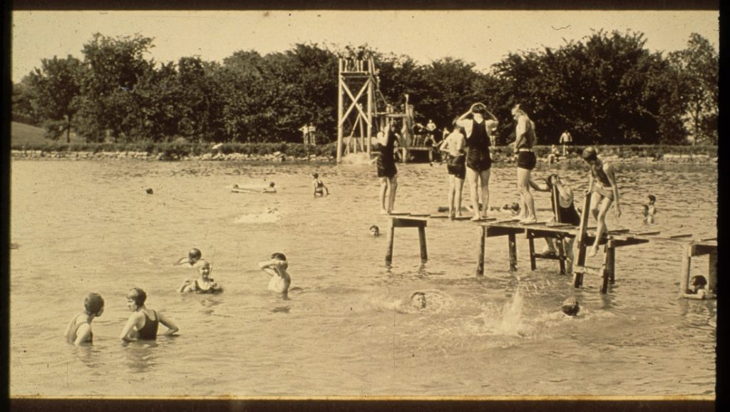 Black-and-white photograph of swimmers. Some stand on a wooden wharf; others stand on stairs of the wooden diving board.