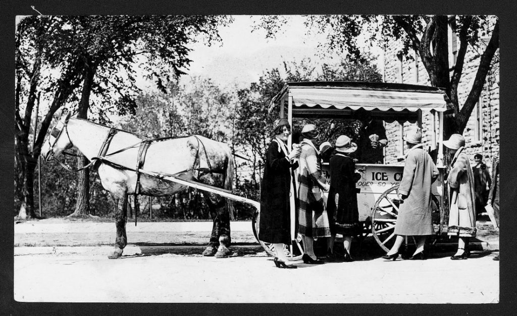 Black-and-white photograph of a horse-drawn wagon with an awning. Standing in front are five women wearing pumps, coats, and cloche hats.