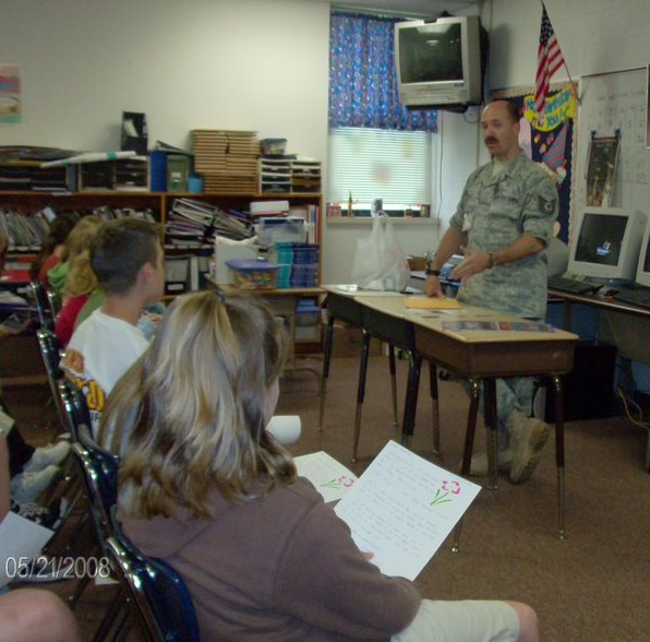 Photograph of a uniformed soldier standing at a desk. The students are sitting in chairs facing him.